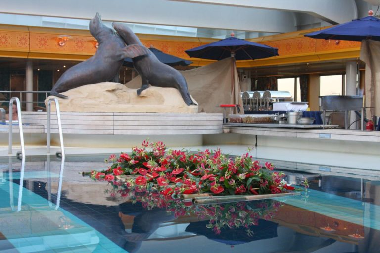 Floating red flower arrangements on pool deck