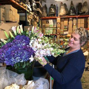 florist holding a purple bouquet